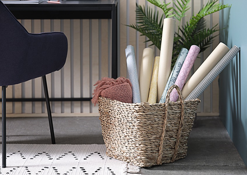 Basket with a throw and rolls of gift wrapping paper