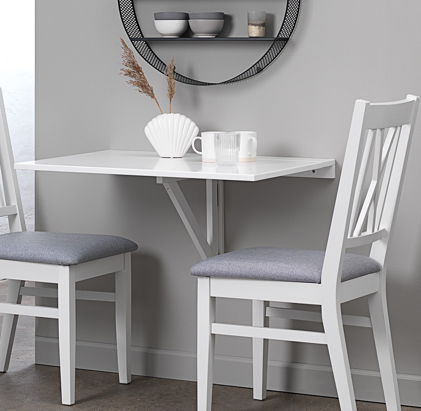 White wall mounted folding table and two dining chairs in kitchen nook