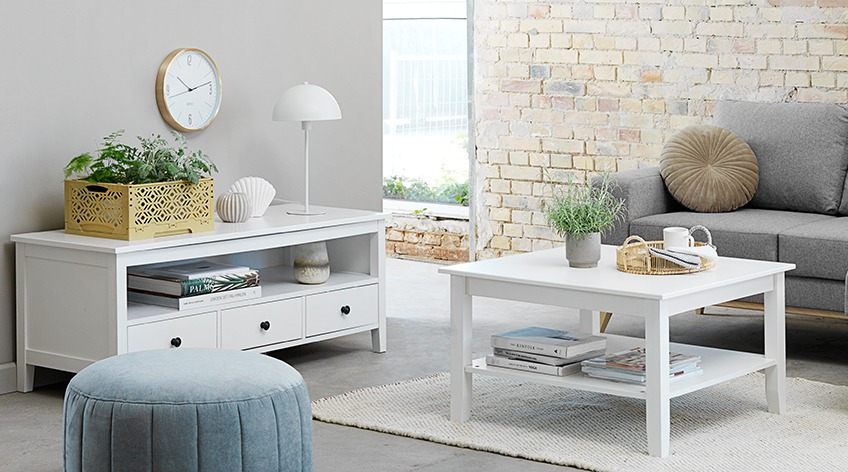 Light living room with white tv stand and coffee table, grey sofa and mint pouffe in the foreground