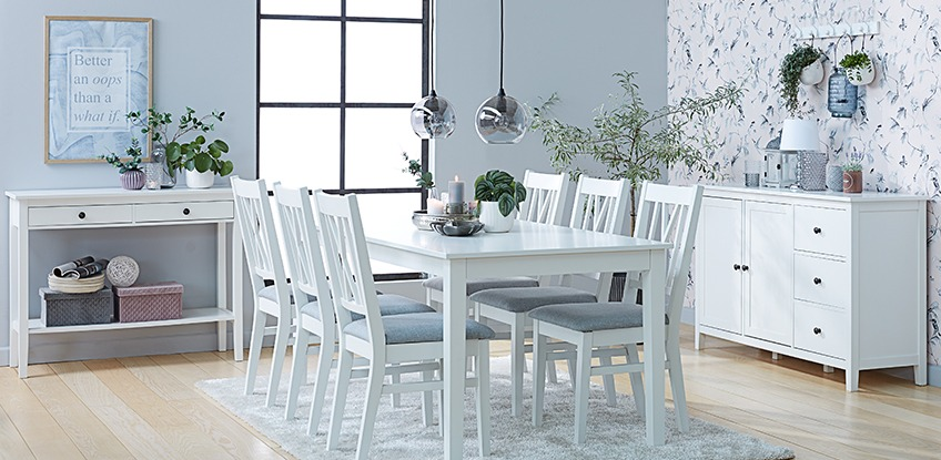 Dining room with all white console table, dining table, dining chairs and sideboard